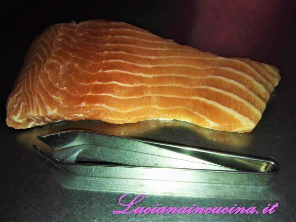 Dopo aver portato a casa un bel filetto di salmone, dividerlo in parti, togliere eventuali spine con l'apposita pinzetta, pulirlo bene ed asciugarlo.