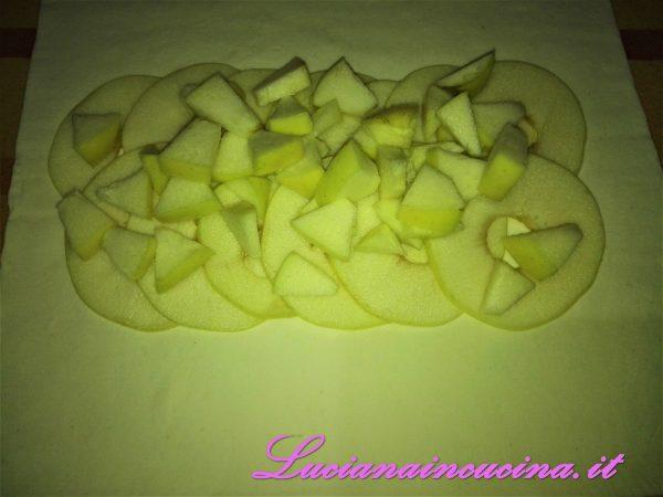 Adagiare le mele affettate e a tocchetti sul rotolo di pasta sfoglia.