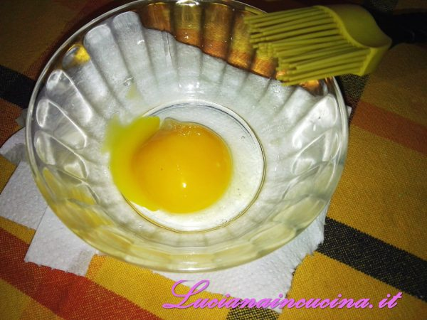 Pennellare la superficie con il tuorlo d'uovo.  Nel frattempo accendere il forno in modalità ventilata a 200°C.