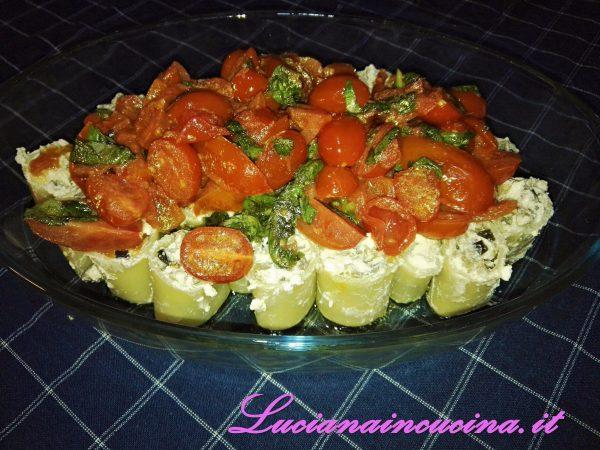 Mettete i paccheri in una teglia da forno leggermente oliata, adagiateli verticalmente uno vicino all'altro, e mettete sopra i pomodorini.