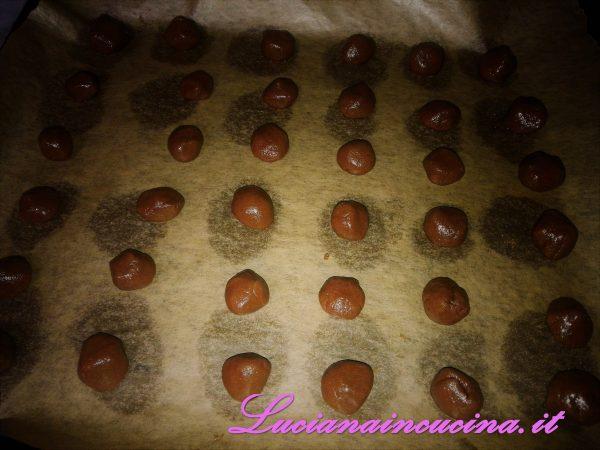 Formare delle piccole palline che verranno adagiate su un foglio di carta forno in una teglia.
