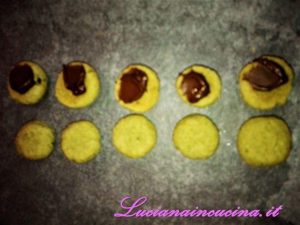 Lasciar raffreddare senza toccare, dopodichè farcire la parte piatta del biscottino con una puntina di Nutella ed unire le 2 sfere.