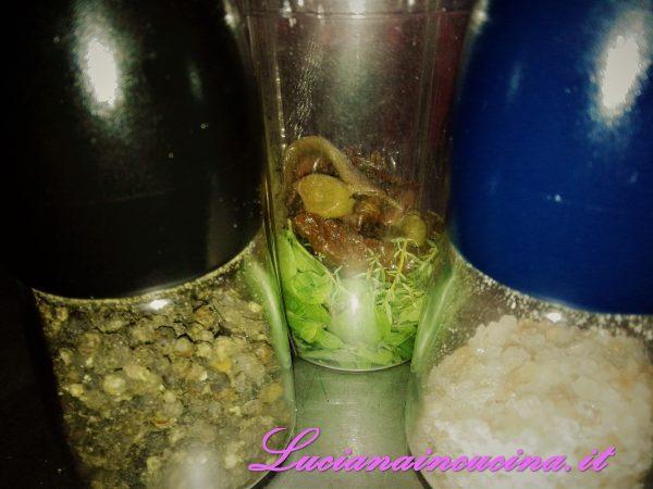 Nel bicchiere del mixer inserire le erbe aromatiche insieme alle alici, le olive, i capperi ed i pomodori secchi e frullare allungando con un filo d'olio