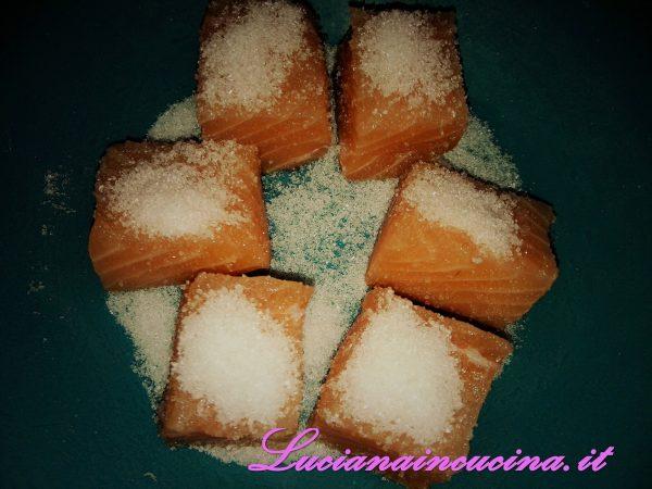 Mischiare il sale e lo zucchero e coprire i dadi di salmone.  Lasciarli marinare per 30 minuti.