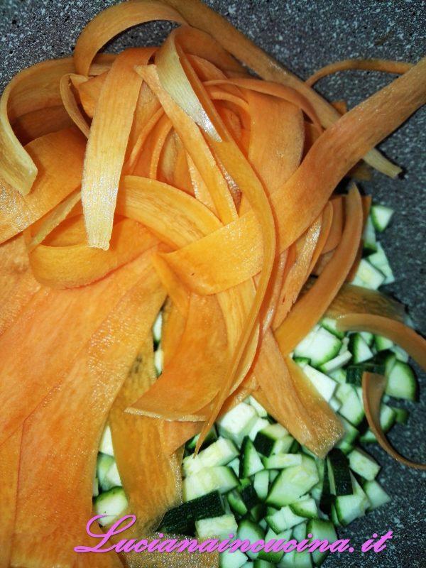 Tagliare le zucchine a tocchetti e le carote a striscioline aiutandovi con un pela patate.