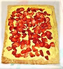 Nel frattempo mondare le fragole e tagliarle a piccoli tocchetti. Montare la panna e comporre il dolce: Svolgere il rotolo ormai raffreddato delicatamente, spalmarne l'interno con la marmellata, la panna ed i pezzetti di fragole. Arrotolare nuovamente e mettere in frigorifero per almeno un'ora.