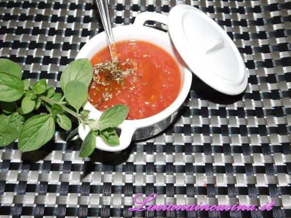 Su ogni fetta mettere un cucchiaio di passata di pomodoro condita con un pizzico di origano.