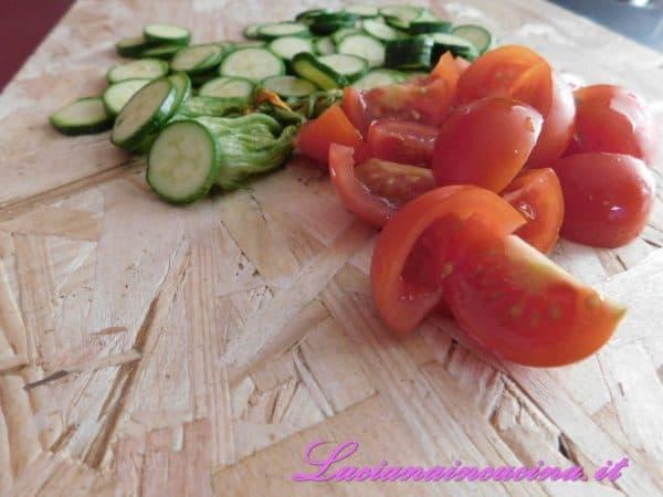 Affettare le zucchine e tagliare i pomodorini in quattro parti.