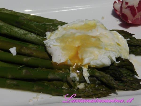 Appoggiare l'uovo sopra gli asparagi insieme al Parmigiano grattugiato ed al burro sciolto.