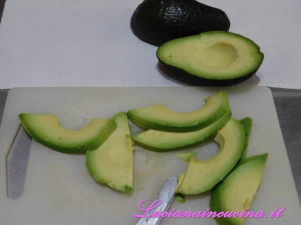 Dividere a metà l'avocado, eliminare il nocciolo, sbucciarlo e tagliarlo a dadini.