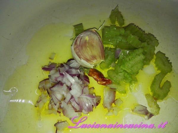 Rosolare in una padella larga, 4 cucchiai di olio con il sedano affettato, l' aglio schiacciato, il peperoncino e la cipolla tritata.