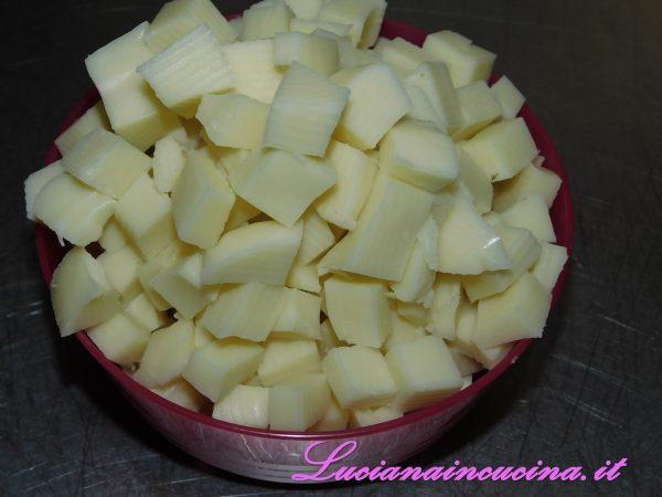 Mischiamo il pesto con la besciamella ormai raffreddata ed il Parmigiano grattugiato . Tagliamo a dadini il formaggio e passiamo ad assemblare la preparazione.