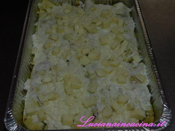 Stendiamo un velo di besciamella precedentemente tenuta da parte, guarniamo con altri dadini di formaggio e spolveriamo di Parmigiano grattugiato.