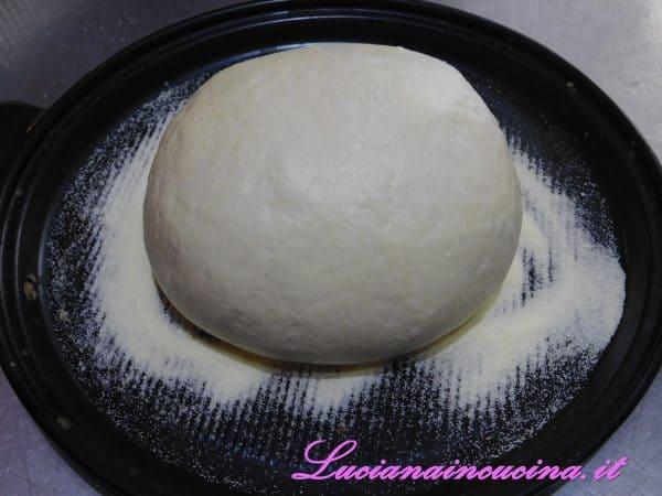 Lavorare l'impasto dando alcune pieghe, poi dargli la forma a palla e adagiarlo sulla base dello stampo cuocipane dove avremo spruzzato un po' di farina.