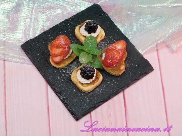 Su ogni pasticcino creare un anello di ripieno alla robiola poi adagiare un fruttino.