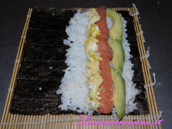Quindi aggiungere una striscia di frittatina ed una di salmone fresco. Bagnare leggermente la parte in fondo dell'alga in modo da saldare l'involtino una volta arrotolato (un po' come si fa per sigillare i nostri ravioli freschi fatti in casa).