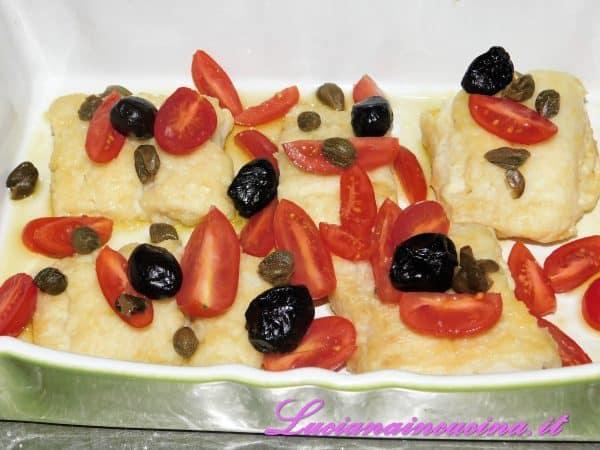 Adagiarvi sopra i filetti di pomodorini divisi in quattro ed aggiungere le olive ed i capperi dissalati.