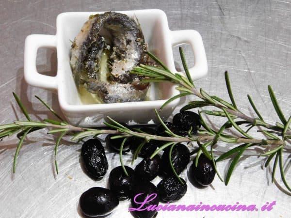 Pulire le alici e denocciolare le olive.