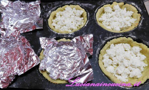 Dopo 10 minuti in forno togliere il foglio di alluminio dalle tartellette.