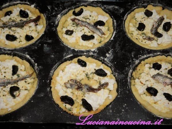 Sbriciolare la ricotta sulle basi di pasta frolla e versarvi il composto di uova e rosmarino, completando con mezza alice al centro e 2 olive divise a metà per ogni tartelletta.