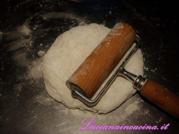 Stendere ogni pezzo di pasta con il matterello.