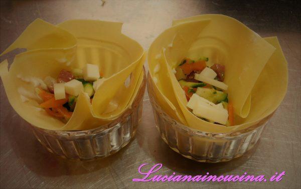 Ungere leggermente le cocottine da forno e foderarle con un foglio di lasagna (se utilizzate quelle sottilissime non occorre prelessarle).  Versare un cucchiaio di besciamella, poi le verdure ed i formaggi (compreso il Parmigiano grattugiato)