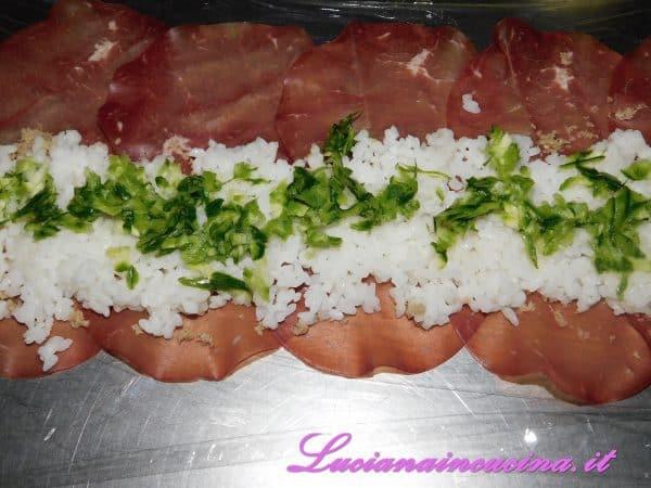 Con le mani inumidite di acqua stendere il riso e poi la zucchina grattugiata.
