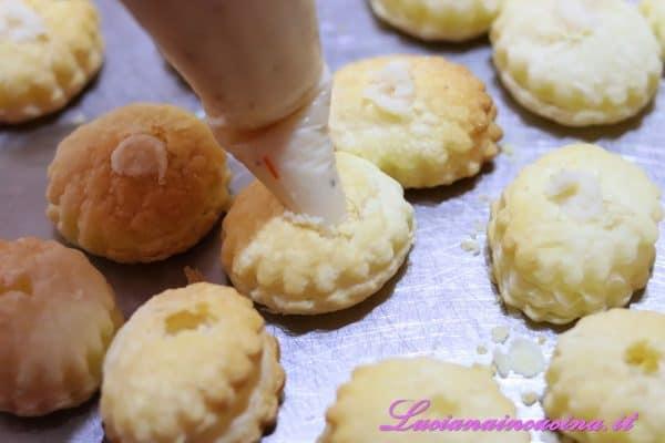 Praticare dei forellini nei dischetti di sfoglia e farcirli con la fonduta di Parmigiano.
