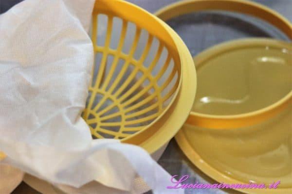 Inserire il setaccio nella ciotola raccogli siero, rivestire l'interno con un canovaccio e fissarlo alla ciotola con l'anello.