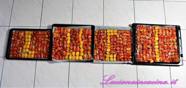 Tagliare in due tutti i pomodorini e disporli in una o più teglie ricoperte da carta forno (mio marito è stato così carino da comporre il mio nome...).