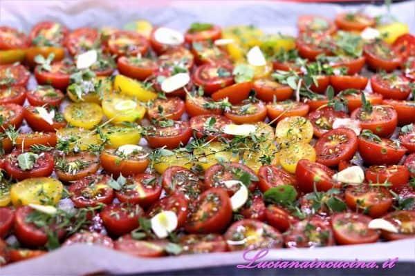 Ora distribuire sopra i pomodorini l'aglio a fettine, l'origano, il timo, lo zucchero, il sale, il pepe ed infine l'olio.