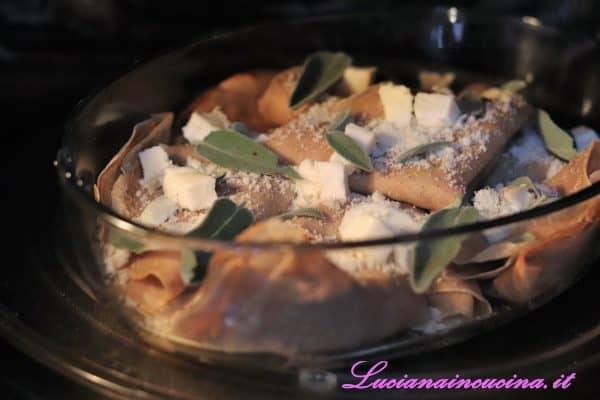 Piegarle a portafoglio e adagiarle in una pirofila da forno leggermente unta d'olio extravergine d'oliva. Guarnirle con qualche foglia di salvia fresca, dei ciuffetti di burro, i cubetti di taleggio rimasti ed una spolverata di Grana Padano.