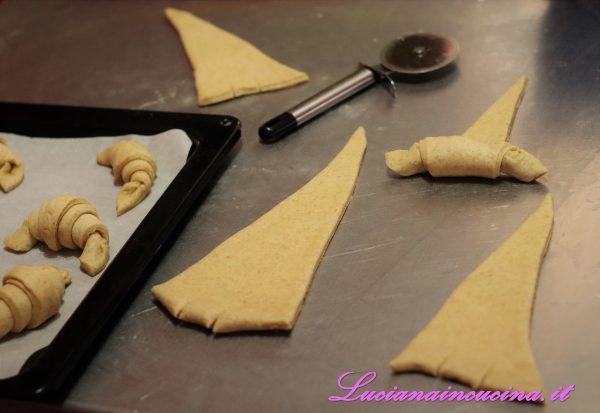 Arrotolare i triangoli su se stessi e formare le brioches.