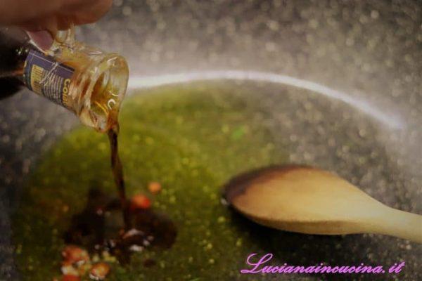Spegnere, togliere le fette d'aglio e versare i peperoncini, l'erba cipollina tagliuzzata e la colatura di alici.