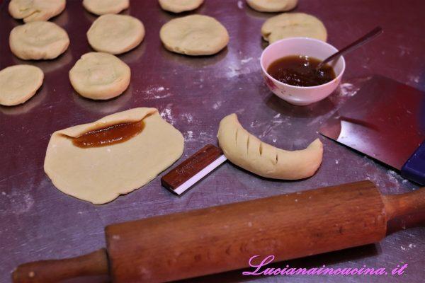 """Dividere l'impasto in 10-12 pezzi, stenderli con il matterello dando una forma circolare, depositare un cucchiaio di marmellata su un lato del disco e poi avvolgerlo dando una forma """"a brioche""""."""