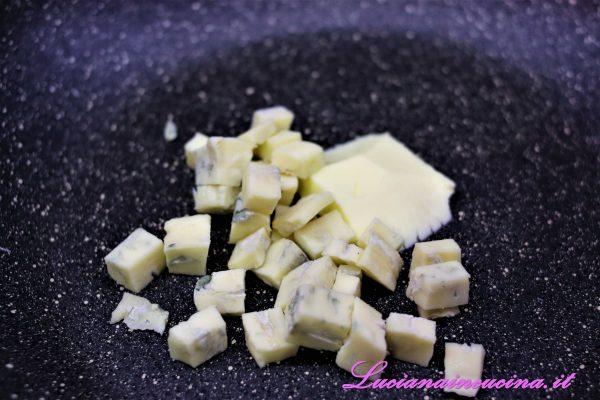 In una pentola wok scaldare il burro e sciogliervi il Gorgonzola tagliato a dadini.