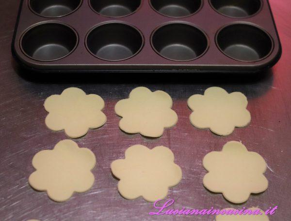 Srotolare la pasta sfoglia e inciderla con un coppapasta a forma di fiore.