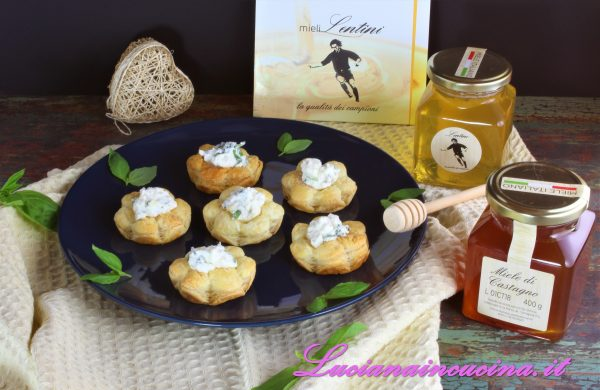 Disporre i fiorellini di sfoglia sul piatto da portata, inserire a ciuffetti la ricotta nel centro di ogni fiore e versare il miele a pioggia.
