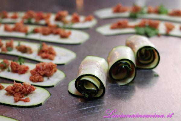 Distribuire sul trito anche delle foglioline di maggiorana fresca e poi arrotolare le zucchine.