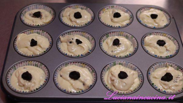 Riempire quasi fino al bordo i pirottini da muffins inseriti nello stampo da forno, appoggiare un'uvetta sulla superficie di ciascuno.