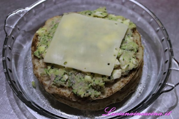 Adagiare una prima crépe nella pirofila, coprirla con uno strato di composto alle zucchine, poi depositare una fetta di fontina.