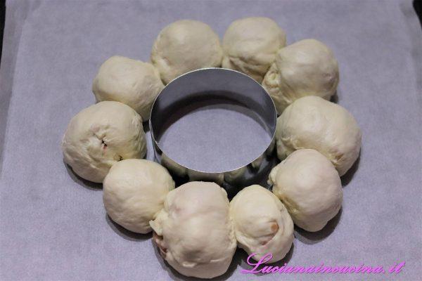 In una teglia da forno mettere al centro un coppa pasta rotondo e disporvi intorno le palline di pasta ripiene.