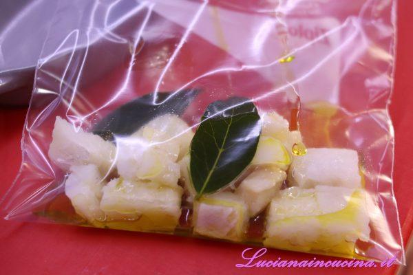 Inserire i pezzetti di baccalà in un sacchetto adatto per la cottura a bassa temperatura insieme a due foglie di alloro e l'olio extravergine d'oliva.