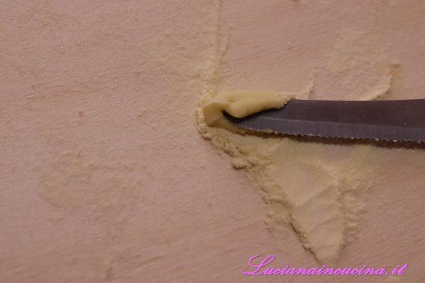 """Tagliare i filoncini ottenuti in piccoli gnocchetti e, usando di piatto la parte non affilata di un coltello, """"strascinarli""""."""