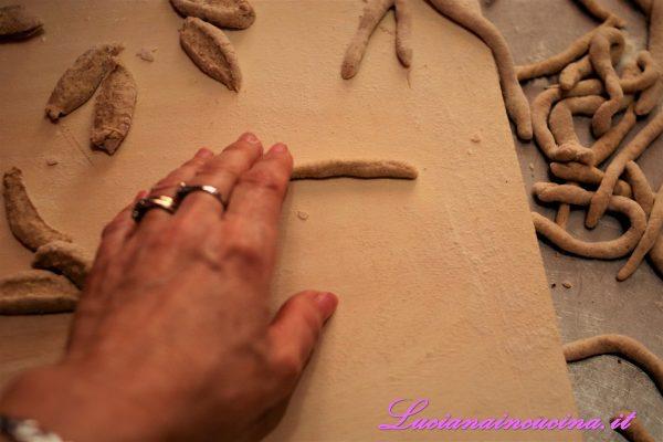 Affettare il filone a tocchetti di mezzo centimetro che andranno fatti rotolare sulla spianatoia formando dei maccheroncini lunghi circa 10 cm.