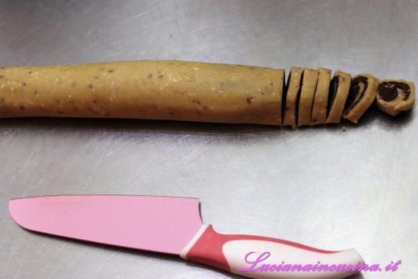 A questo punto tagliare a fette il rotolo bicolore ricavando i biscotti.