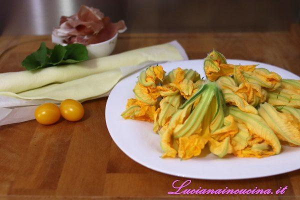 Pulire i fiori di zucchina eliminando il peduncolo, il pistillo, i sepali e mantenendo solamente i petali.