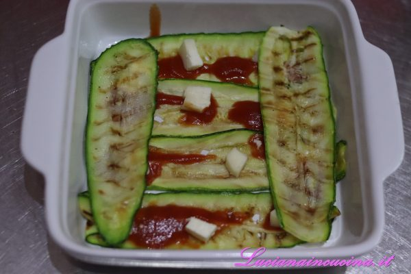 Insaporire con la passata di pomodoro ed un po' di formaggella, poi continuare con gli strati di zucchine incrociandole ogni volta e aggiungendo anche il taleggio ed il formaggio grattugiato.