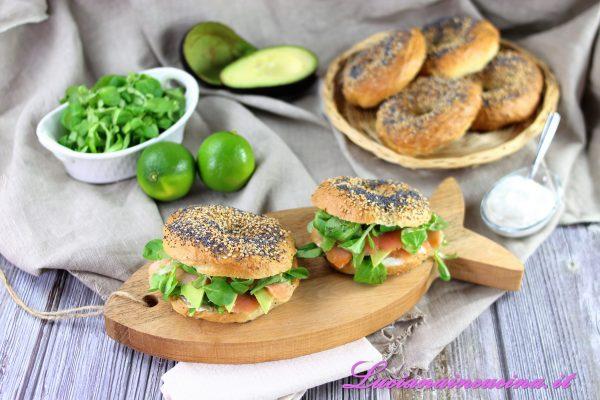 Tagliare a metà il bagel, farcirlo con la panna acida, qualche fetta di avocado, il salmone affumicato, un pò di insalata e richiudere il panino.