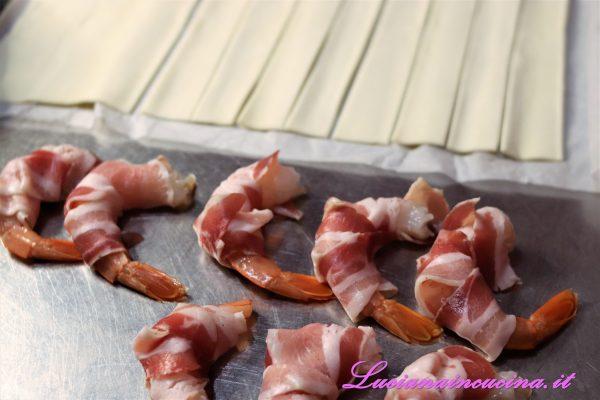 Avvolgere le code dei gamberi nelle fette di pancetta lasciando libera la parte finale del codino.